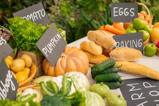 Gros plan de pain blanc et légumes frais placés sur le comptoir avec des étiquettes en épicerie biologique