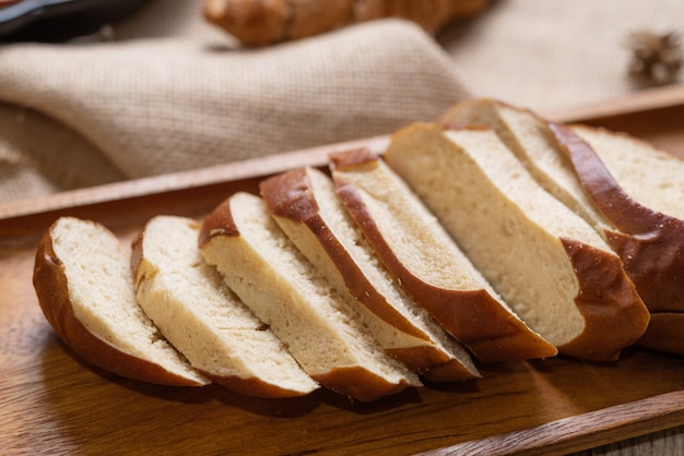 Gros plan de pain de blé entier fait maison mis sur la plaque de bois.
