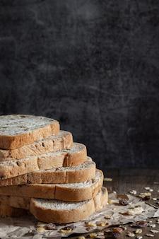 Gros plan pain de blé entier à grains tranchés sur fond de bois rustique foncé, ingrédients bio, aliments sains.