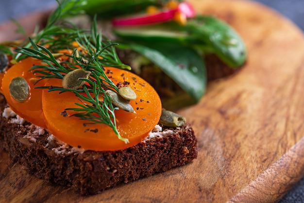Gros plan de pain grillé avec du fromage cottage et tomate jaune, graines de citrouille, verts sur planche de bois, concept de collation végétarienne saine