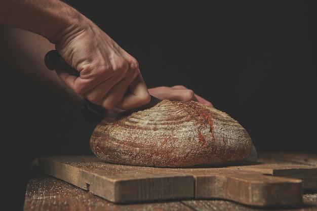 Gros plan d'un pain rond frais tranché à la main d'un boulanger