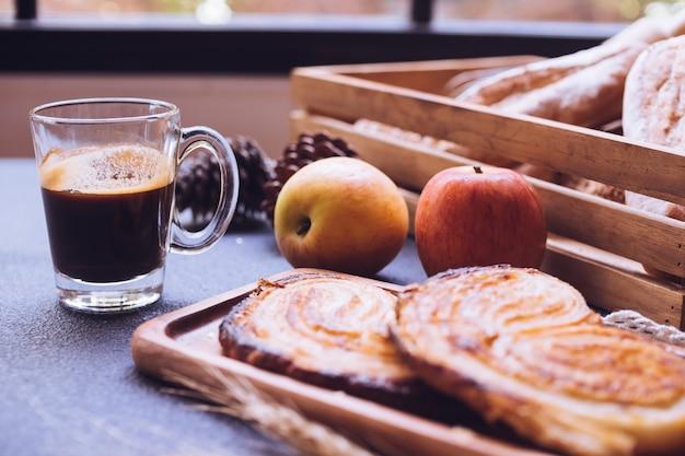 Gros plan de pains cuits au four, des pommes et une tasse de café sur une table.