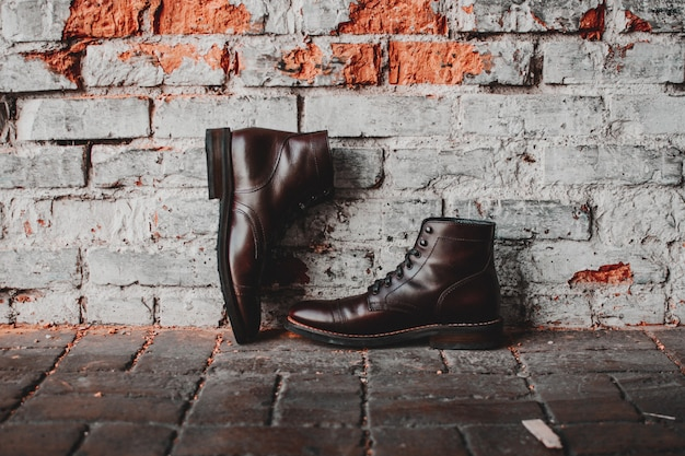 Un gros plan d'une paire de chaussures classiques sur un mur de briques