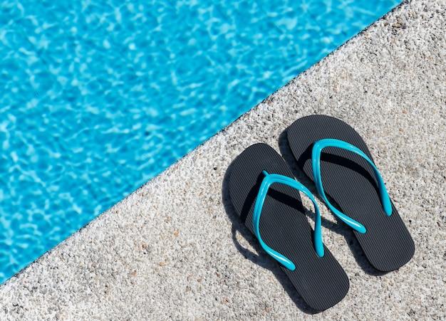 Gros plan d'une paire de tongs au bord d'une piscine. copiez l'espace. vue de dessus.