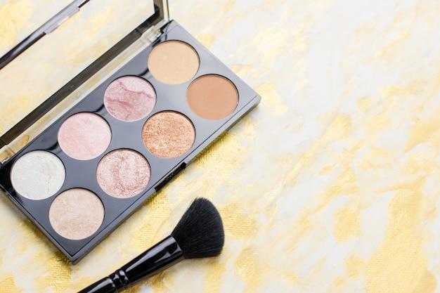 Gros plan de palette surligneur, maquillage cosmétiques en noir et or.