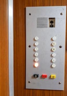 Gros plan sur le panneau de boutons de l'ancien ascenseur, cadre vertical.