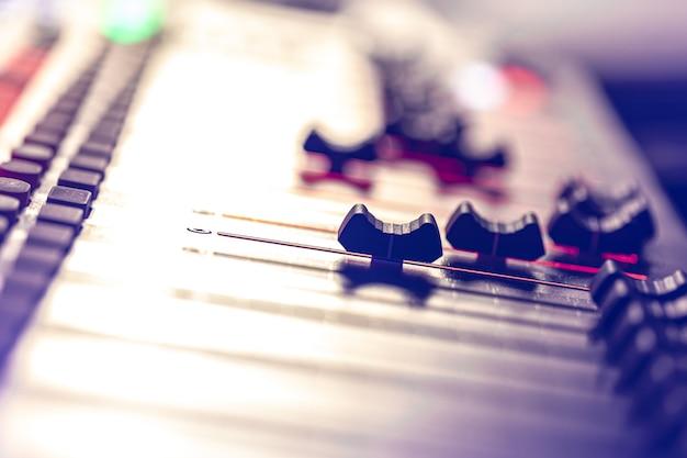 Gros plan, panneau de commande du mixeur de musique sonore sur fond flou.