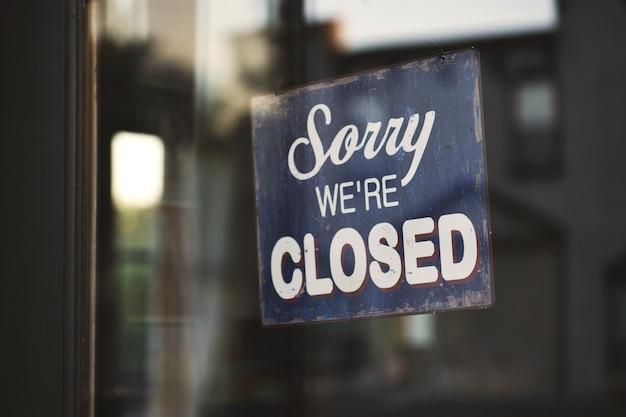 Gros plan d'un panneau indiquant «désolé, nous sommes fermés» accroché à une porte en verre