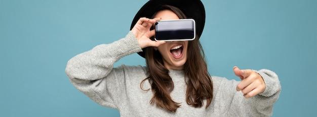 Gros plan panoramique d'une jeune femme heureuse séduisante portant un chapeau noir et un pull gris tenant un téléphone pointant le doigt vers la caméra isolée sur fond. maquette, découpe, espace vide