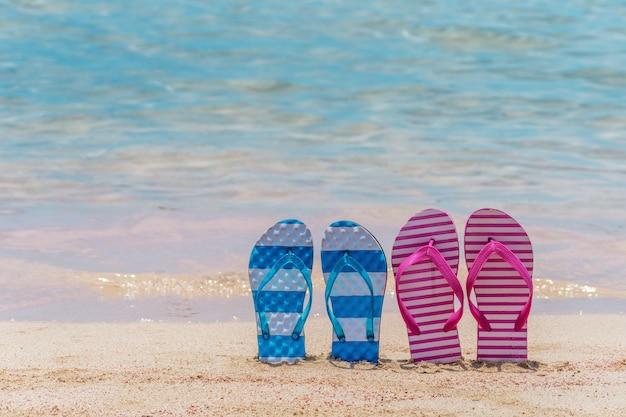 Gros plan sur des pantoufles sur une plage tropicale