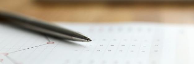Gros plan, de, papier affaires, pose bureau, à, stylo argent. graphique et diagramme avec des nombres. recherche de revenus et dépenses. concept de paperasse et de comptabilité