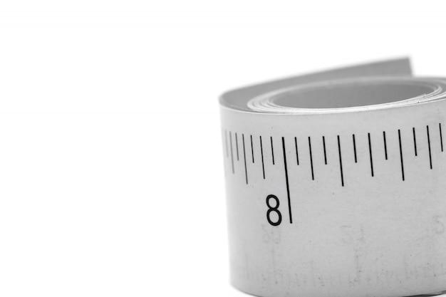 Gros plan papier rouleau de ruban à mesurer isolé sur fond blanc avec espace de copie