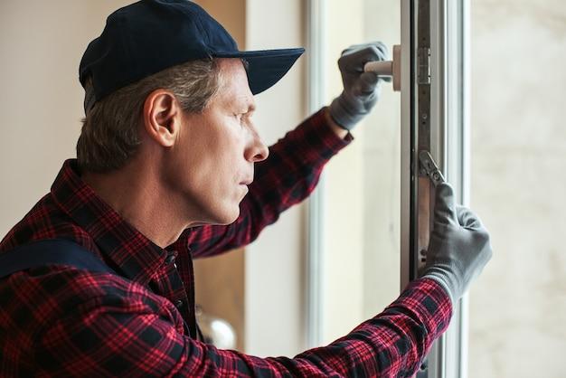 Gros plan sur les paramètres sensibles du bricoleur senior définissant de nouvelles fenêtres