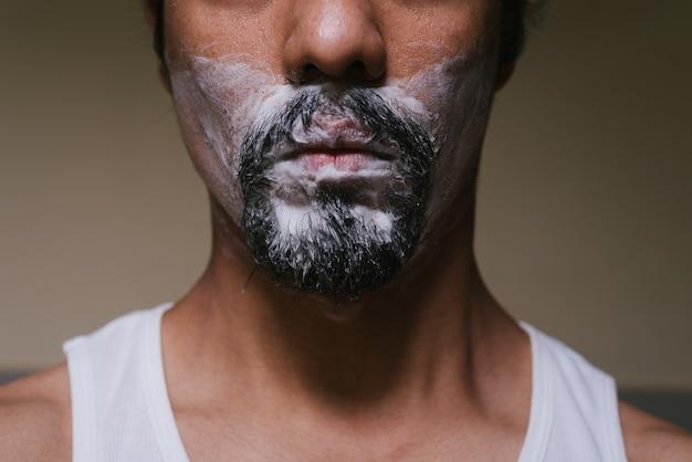Gros plan d'une partie du visage d'un homme latino qui a de la mousse sur sa barbe et porte des sous-vêtements