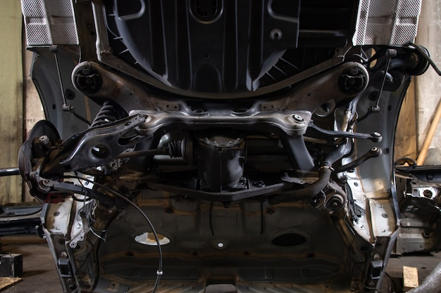 Gros plan, partie sciée d'une vieille carrosserie: soubassement, suspension arrière multibras, freins à disque, bras de suspension, tuyaux de frein dans un ancien garage. analyser jankyard