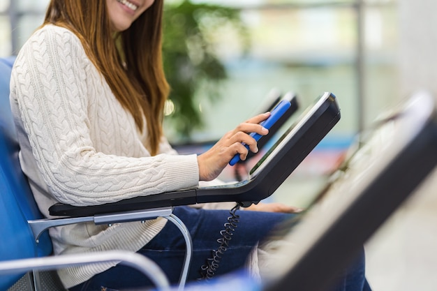 Gros plan passager main tenant et balayant le téléphone mobile avec machine de scanner de code qr de chaise de message à l'aéroport