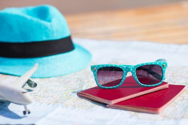 Gros plan de passeports, avion jouet, lunettes de soleil sur la carte
