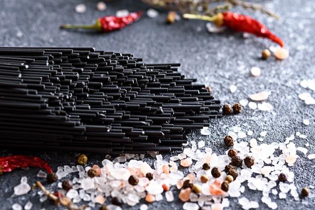 Gros plan pâte noire avec sel de mer rose et piment rouge sur fond gris