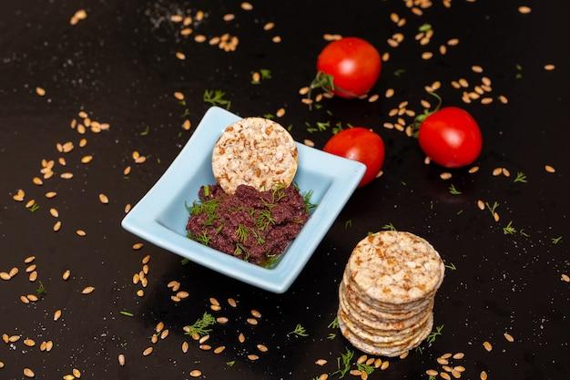 Gros plan de pâte d'olive dans un bol sur la table avec des craquelins et des tomates sous les lumières