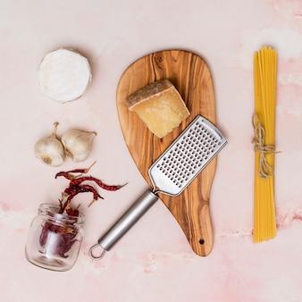 Gros plan, pâtes crues fromage; piment séché; ail et ustensiles de cuisine sur fond rose