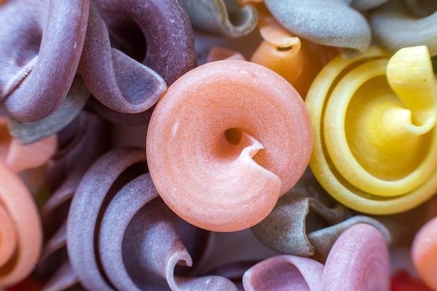 Gros plan des pâtes nues sèches crues sèches pâtes abstraites. ingrédient populaire de la cuisine traditionnelle italienne, nutrition, concept de régime sain et savoureux.