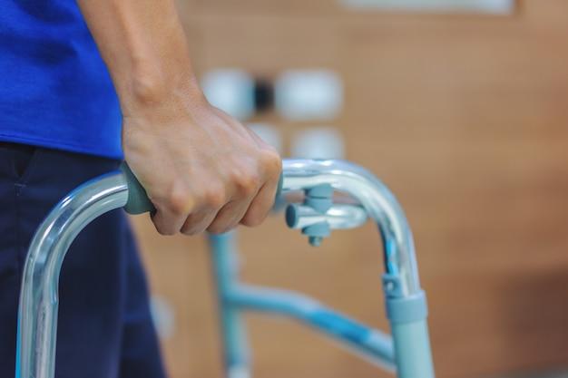 Gros plan, un patient d'âge moyen utilise des marcheurs pour s'exercer à marcher après la chirurgie.