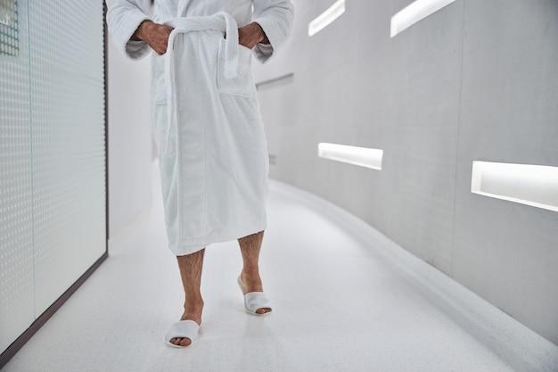 Gros plan sur un patient masculin en peignoir blanc gardant les mains dans les poches tout en passant du temps dans une clinique de bien-être moderne