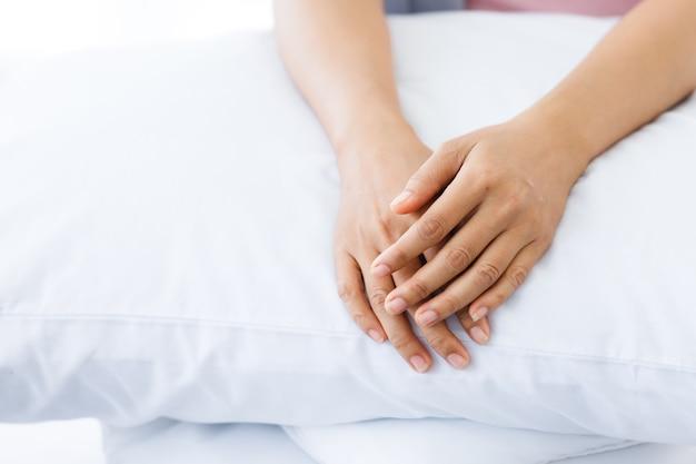 Gros plan sur une patiente atteinte d'un cancer du sein avec un ruban rose portant un foulard après le traitement à la chimiothérapie, s'asseoir sur le lit dans la chambre à coucher à la maison, soins de santé, concept de médecine