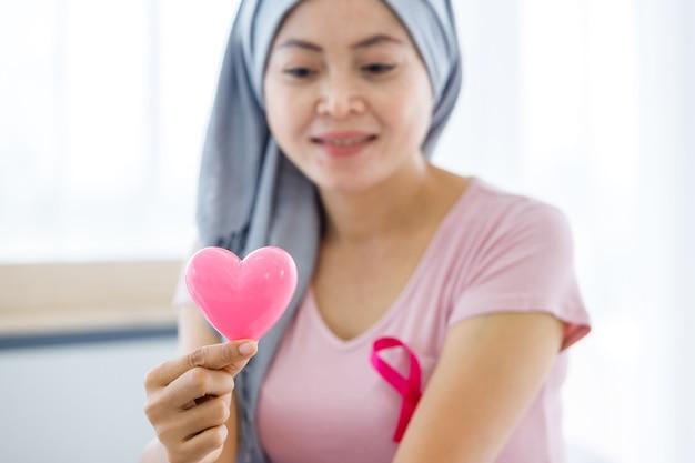 Gros plan sur une patiente atteinte d'un cancer avec un ruban rose portant un foulard après un traitement à la chimiothérapie avec la tenue d'un petit coeur rose en forme à la maison, concept de médecine