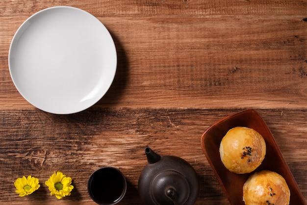 Gros plan de la pâtisserie jaune de gâteau de lune, gâteau de lune pour les vacances de la fête de la mi-automne sur fond de table en bois
