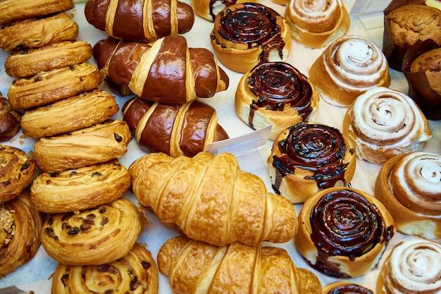 Gros plan de pâtisseries fraîches au four sur une vitrine de boulangerie.