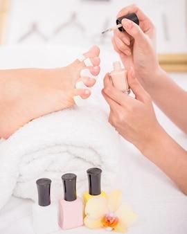 Gros plan d'un pédicure appliquant du vernis à ongles sur les ongles des pieds.