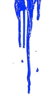 Gros plan de la peinture bleue qui coule isolé sur fond blanc. composition verticale