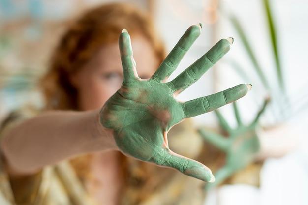 Gros plan de peinture verte sur la paume de la femme