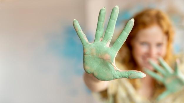 Gros plan de peinture verte sur les paumes de la femme