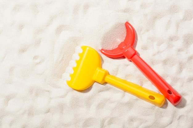 Gros plan d'une pelle rouge et d'un râteau jaune sur le sable.