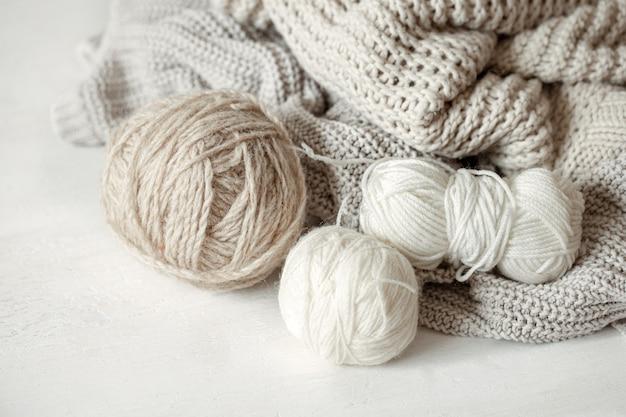Gros plan sur des pelotes de laine aux couleurs pastel et un pull confortable en tricot