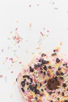 Gros plan de pépites colorées et pépites de chocolat sur le beignet sur fond blanc