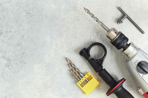 Gros plan sur une perceuse électrique et des forets incassables sur du béton avec espace de copie
