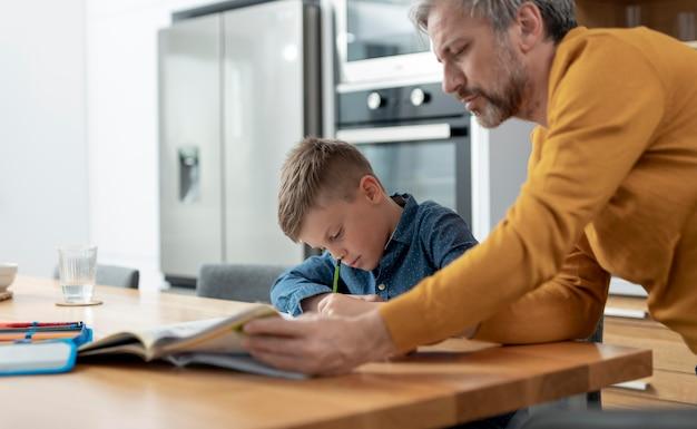 Gros plan père aidant enfant à faire ses devoirs