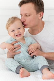Gros plan père embrassant enfant en bas âge