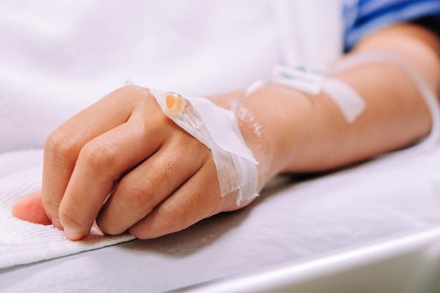 Gros plan d'une perfusion intraveineuse dans la main du patient à l'hôpital.