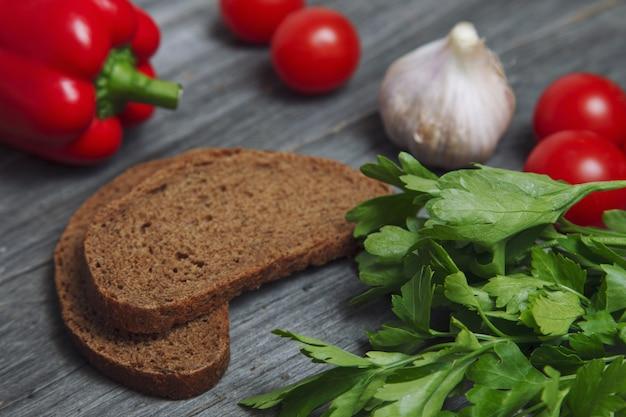 Gros plan de persil sur une table en bois avec des légumes et du pain