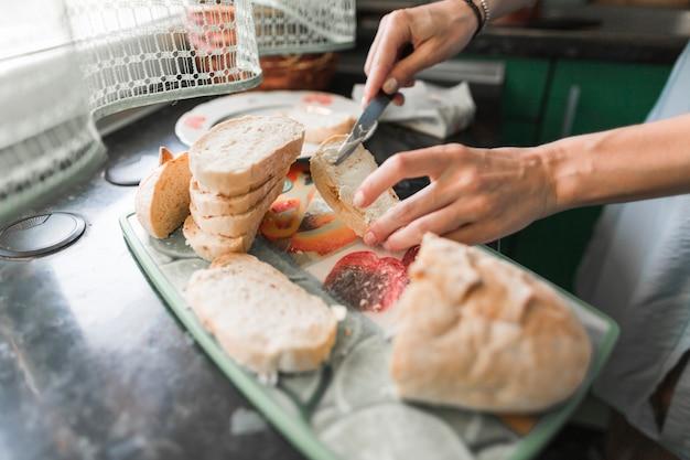Gros plan d'une personne appliquant du fromage sur des tranches de pain