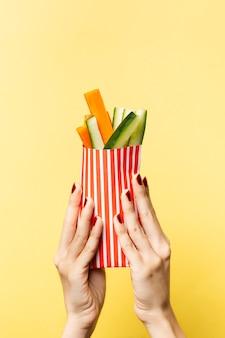 Gros plan personne brandissant des légumes