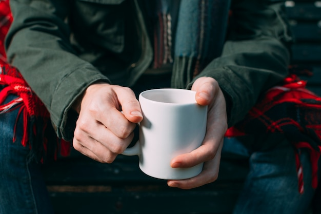Gros plan personne brandissant une tasse blanche
