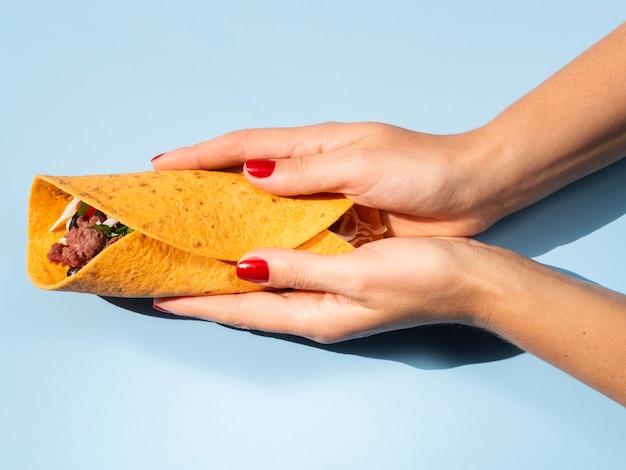 Gros plan personne avec burrito délicieux et fond bleu