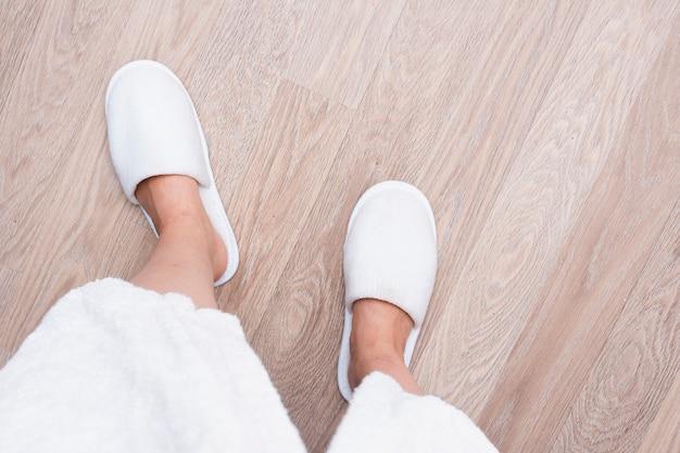 Gros plan personne avec des chaussures blanches sur plancher en bois