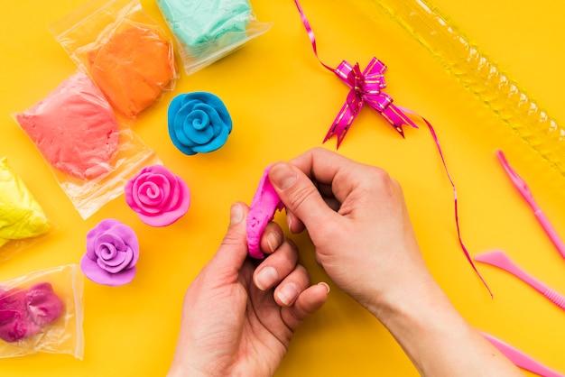 Gros plan, personne, confection, argile colorée, rose, toile jaune, toile de fond
