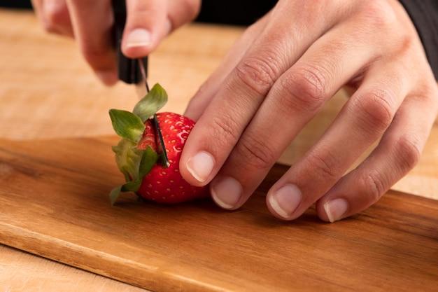 Gros plan personne coupant des fraises